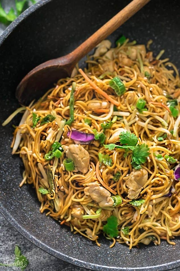 Close-up top view of Chicken Chow Mein in a wok with a wooden spoon