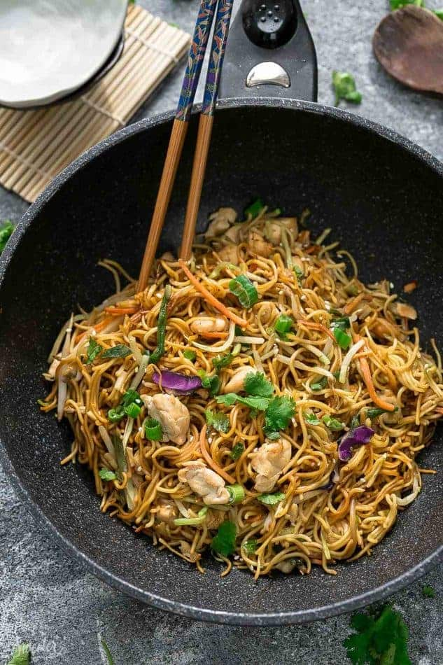 Top view of Chicken Chow Mein in a black wok with chopsticks