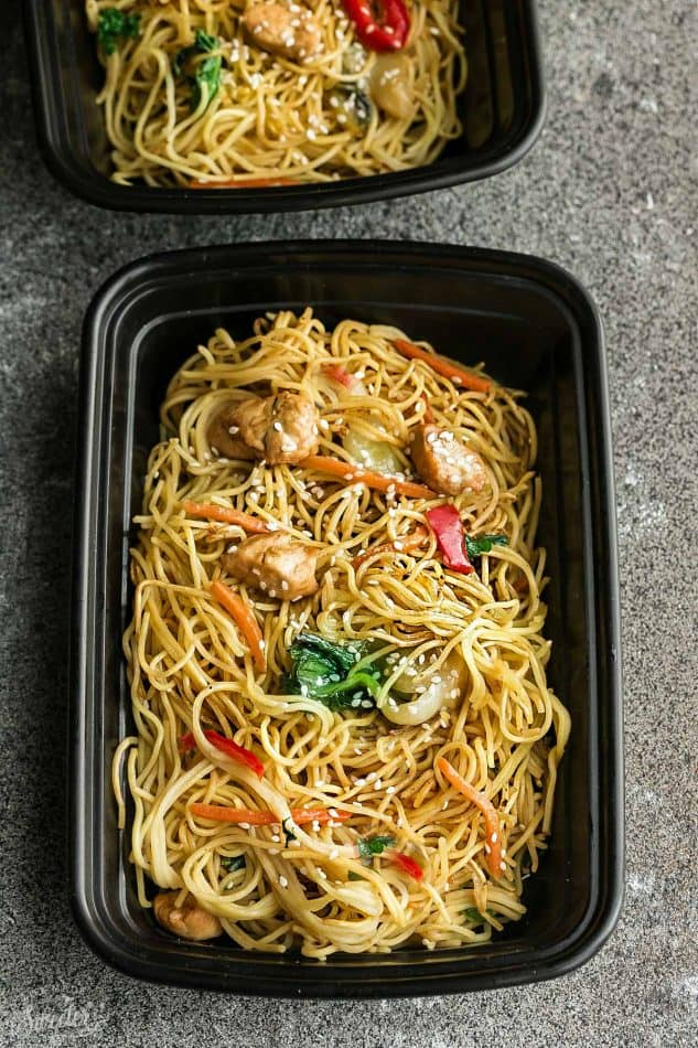 Top view of chicken chow mein in a black meal prep lunch container