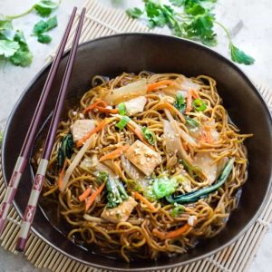 A serving of Chicken Chow Mein in a brown bowl with chopsticks