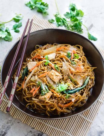 Easy Chicken Chow Mein recipe in a large bowl with brown wooden chopsticks on top.