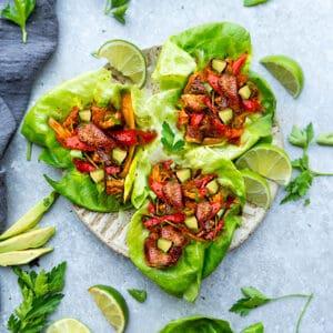Top view of chicken fajita wraps in lettuce on a beige plate on grey background