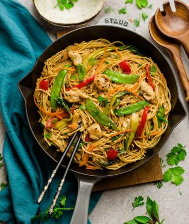Easy Chicken Lo Mein noodles recipe in a large cooking skillet with beautiful chopsticks for a perfect meal.