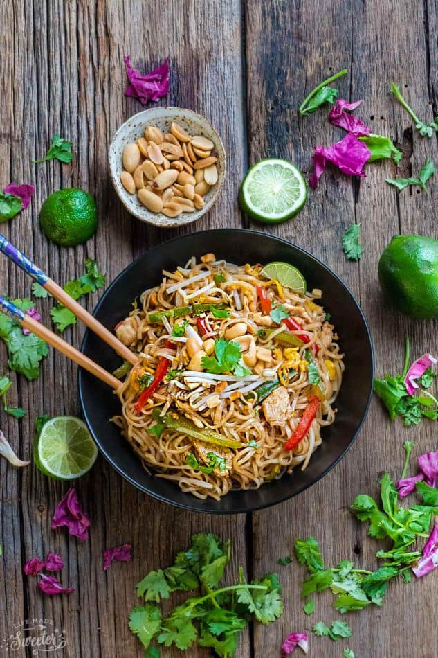 Delicious Chicken Pad Thai recipe and beautiful wooden chopsticks on a wooden table.