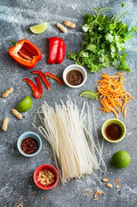 Top view of ingredients to make thai noodles on a grey board