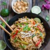 Top view of chicken pad thai in a bowl with chopsticks