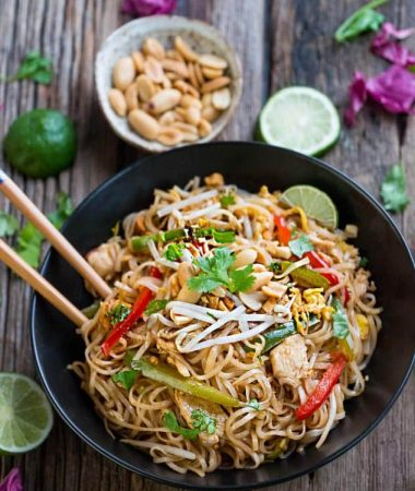Authentic Chicken Pad Thai in a large black bowl with wooden chopsticks on a wooden table.