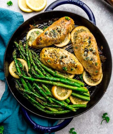 Top view of Easy Chicken Piccata with asparagus and capers in a blue cast iron pan on a grey background
