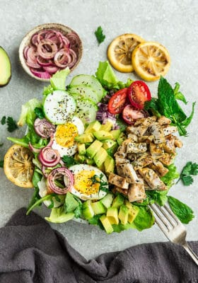Top view of Chicken Shawarma Salad on a white bowl with avocado, hard boiled eggs with a fork on a grey background with grilled lemon slices