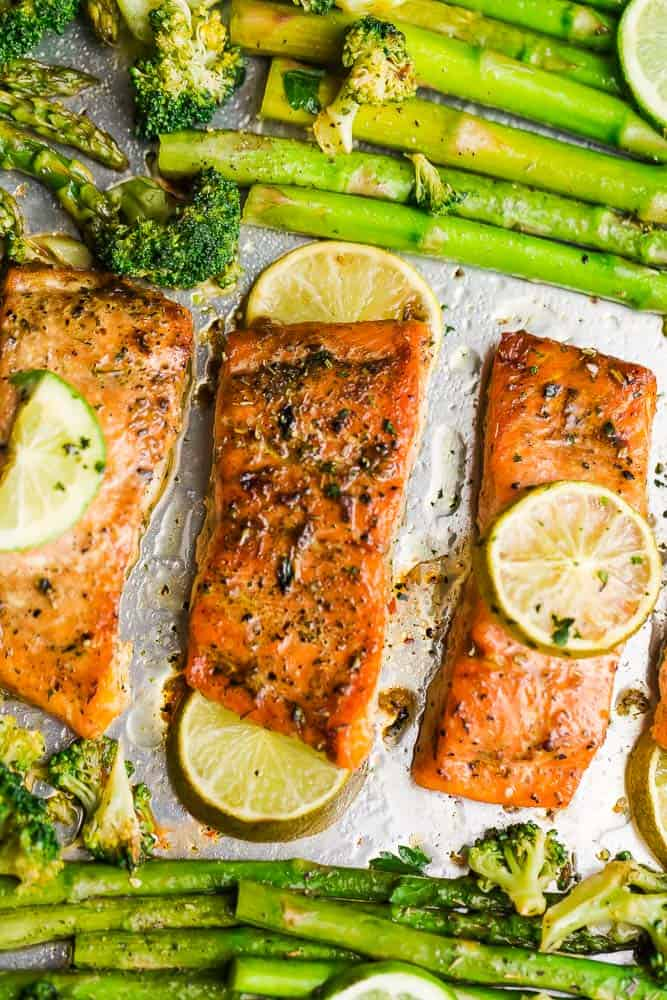 Close-up overhead view of Chili Lime Salmon fillets with broccoli and asparagus on a sheet pan