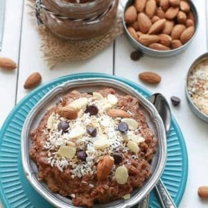 Top view of a bowl of Chocolate Coconut Almond Overnight Oats next to ingredients