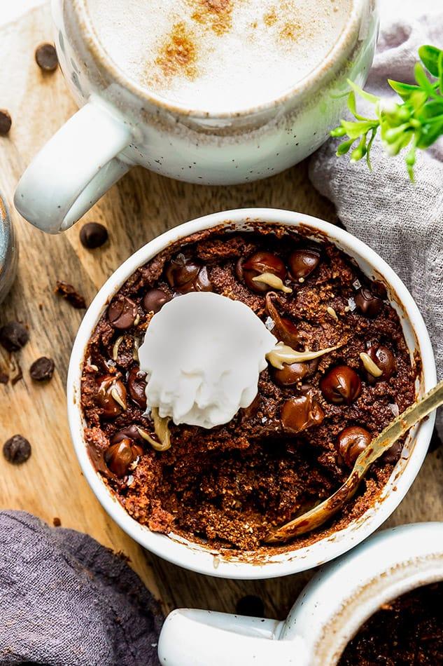 Top view of vegan keto chocolate mug cake with whipped coconut cream in a white mug