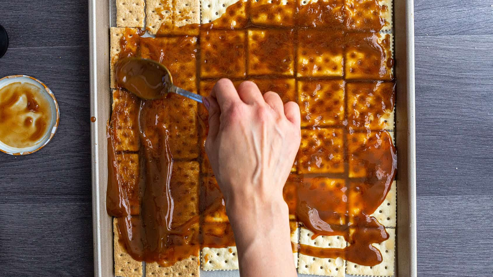 Toffee being spread over crackers on a sheet pan