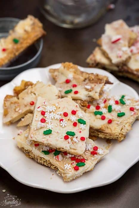 Side view of easy Christmas crack on a white plate with holiday sprinkles