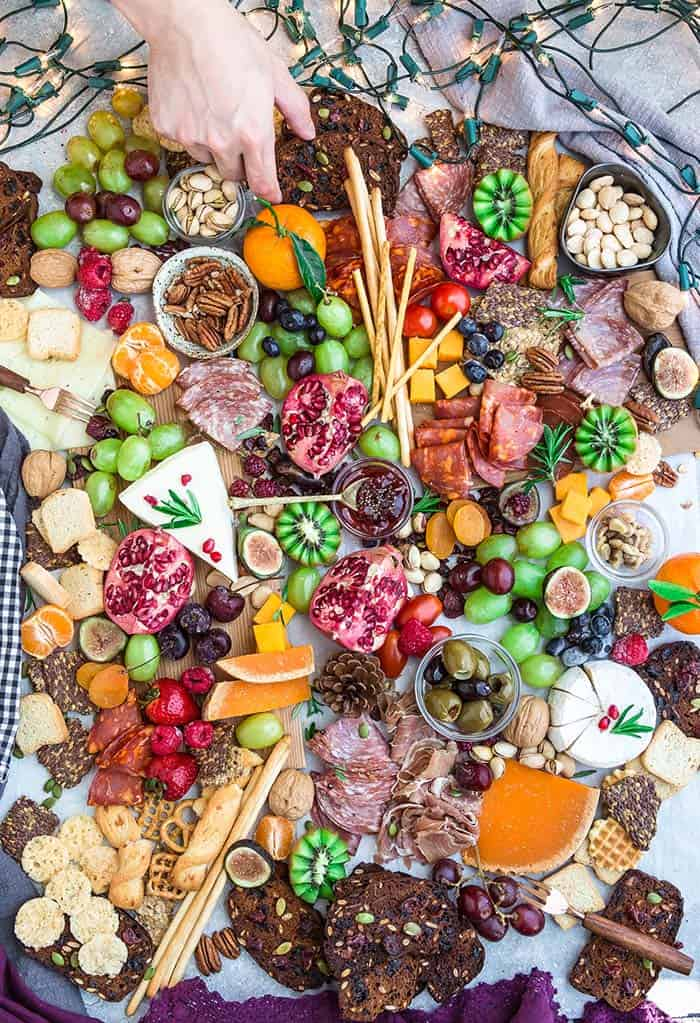 Top view of a variety of crackers, fruits, nuts, meats and cheeses on a holiday charcuterie board
