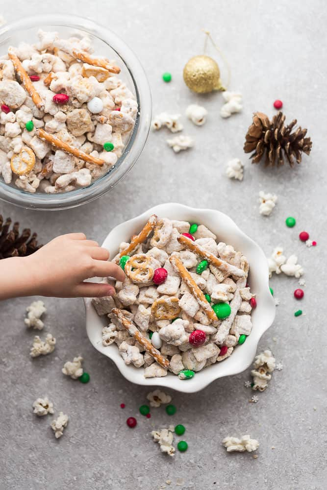 Reindeer Munch - the perfect easy sweet and salty snack to munch on at holiday parties or while watching Christmas movies. Best of all, this simple mix is fun to make with popcorn, Rice Chex cereal, cashews, peanut butter, pretzels and festive M&M's.