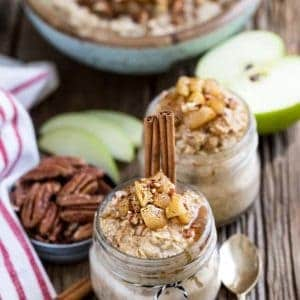 Two jars of Cinnamon Apple Pie Overnight Oats next to a bowl of pecans, apple slices, and utensils