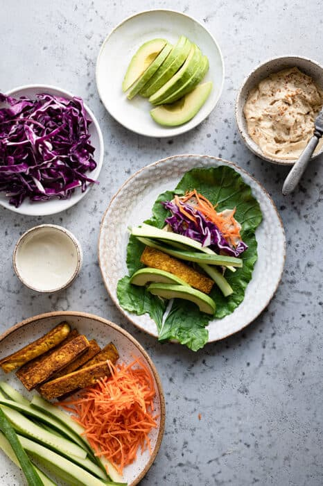 Top view of ingredients to make healthy collard wraps on a white plate with fresh vegetables on the side
