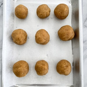 Top view of cookie dough balls on a parchment lined baking sheet