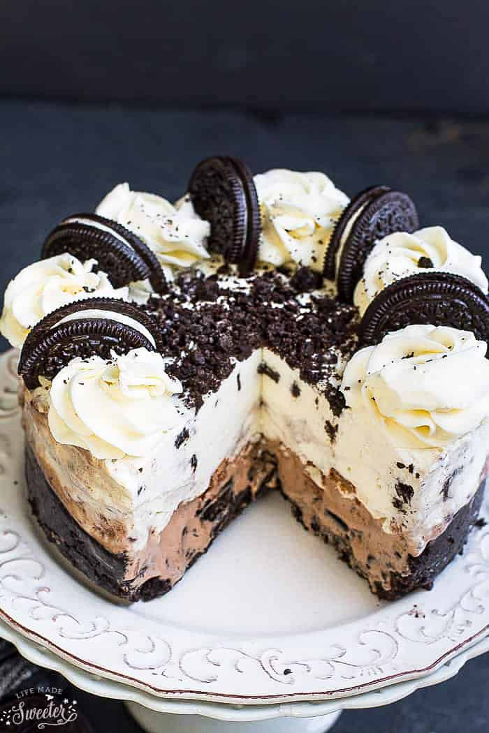 Side view of a sliced Oreo Ice Cream Cake on a white plate