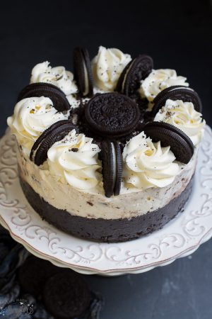Delicious Cookies and Cream Oreo Ice Cream Cake topped with whole oreos on a white cake plate.