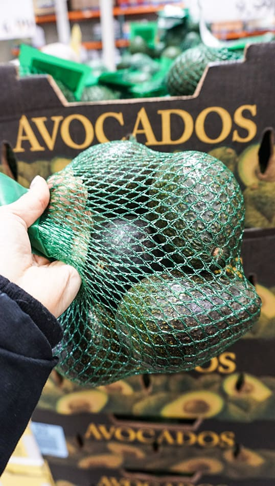 Front view of one bag of green avocados.