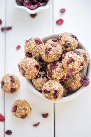 No Bake Cranberry Coconut Energy Bites in a small white bowl on a white wooden table.