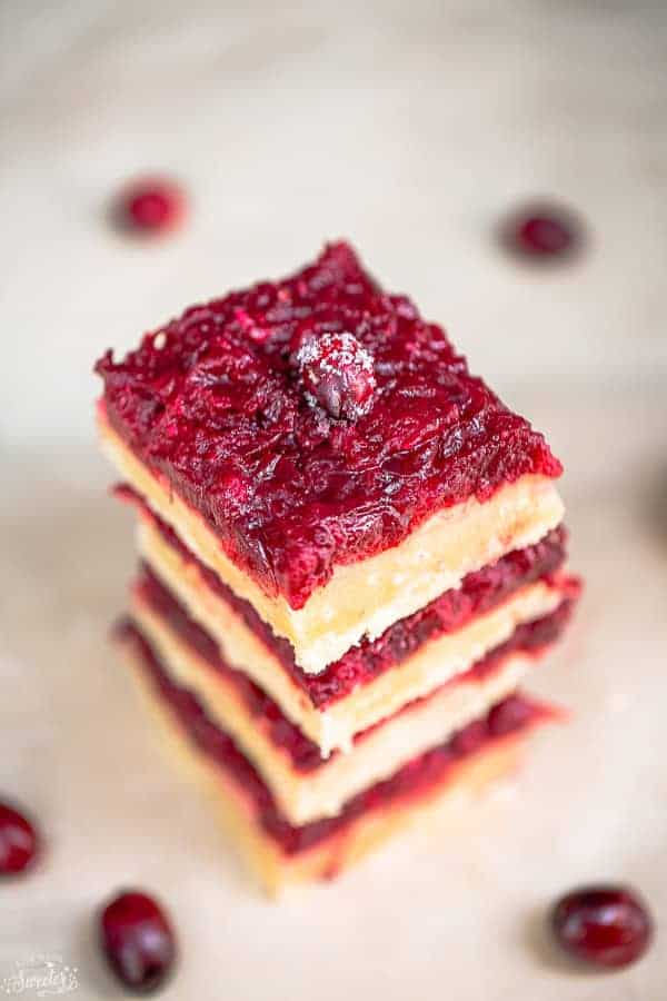 Side view of a stack of cranberry sauce bars on a white background