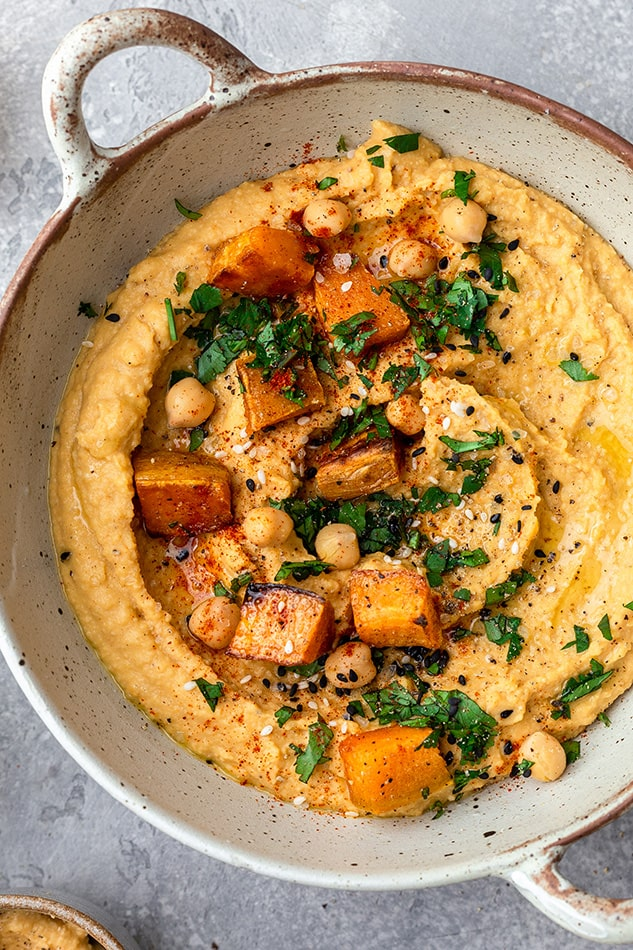 Close-up of sweet potato hummus in a dish topped with cubes of sweet potato, chickpeas and fresh herbs
