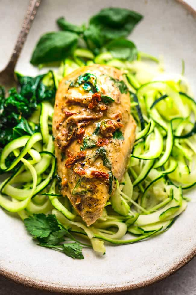 Close up of Creamy Sun-Dried Tomato Chicken Breast over zucchini noodles on plate