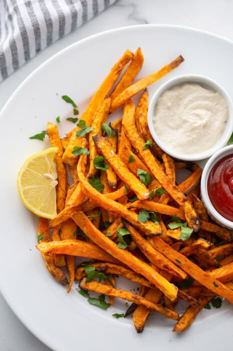 Side view of air fryer sweet potato fries on a white plate with ketchup and aioli