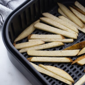 A batch of uncooked french fries in an air fryer basket