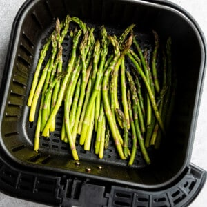 Top view of uncooked asparagus in an air fryer basket