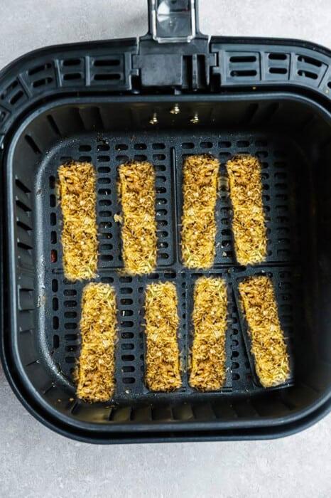 Top view of avocado fries in air fryer basket