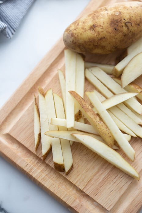 Potatoes cut into french fry slices on a wooden cutting board