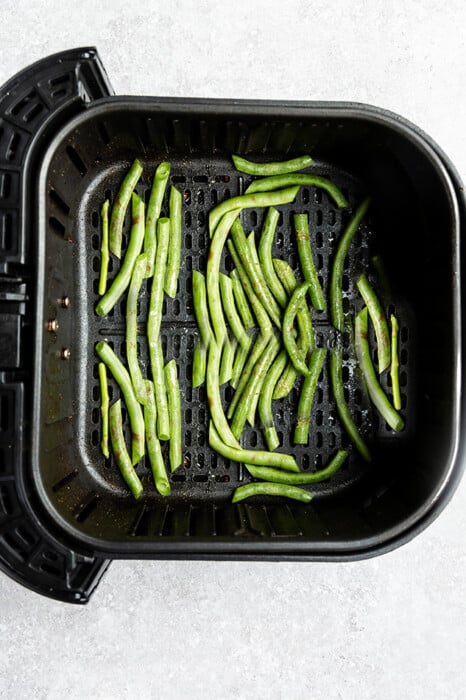 Top view of raw green beans in an air fryer basket