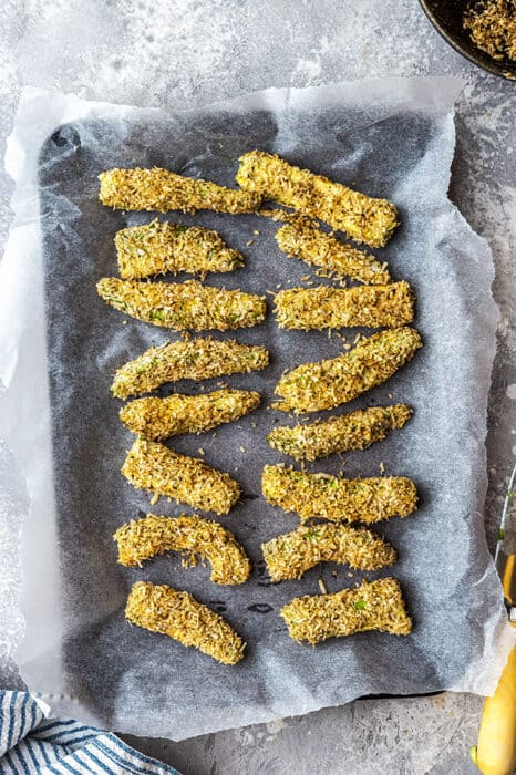 Top view of coated raw avocado fries on parchment paper on a baking sheet