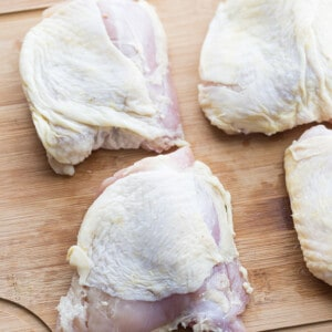 Four raw chicken thighs on a wooden cutting board