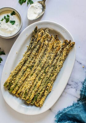 Top view of healthy asparagus fries in a white oval dish