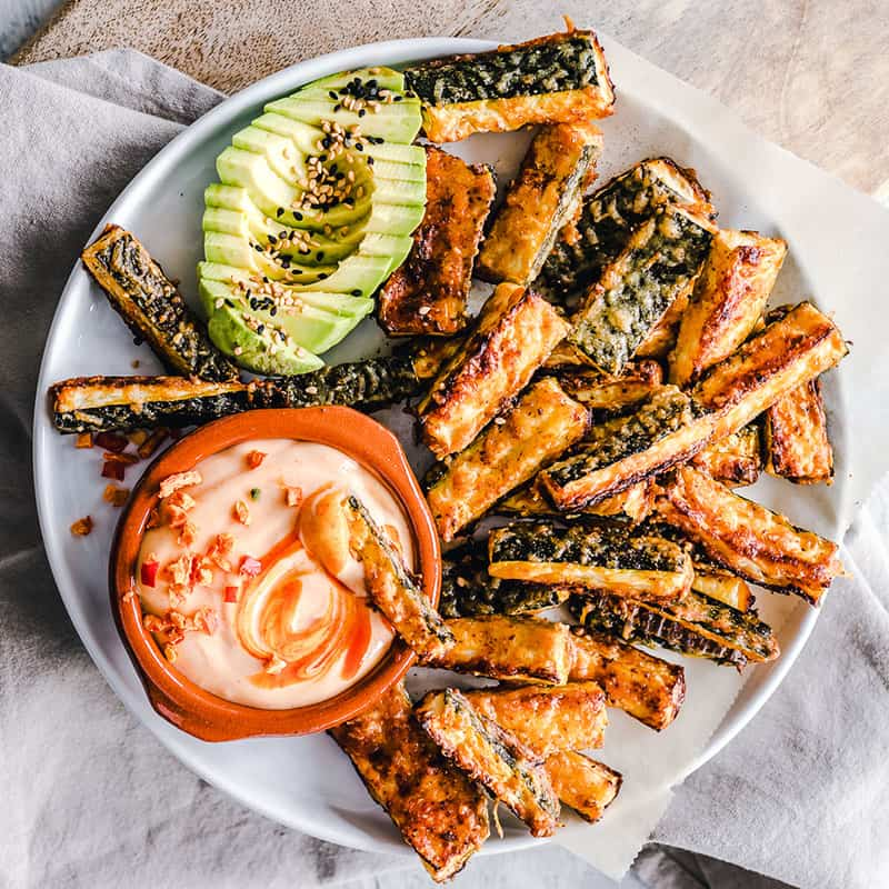 Top view of crispy baked zucchini fries on a white bowl with a bowl of dip and avocado slices