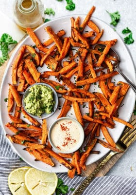 Top view of crispy sweet potato fries on a white oval plate with avocado dip and cashew dip