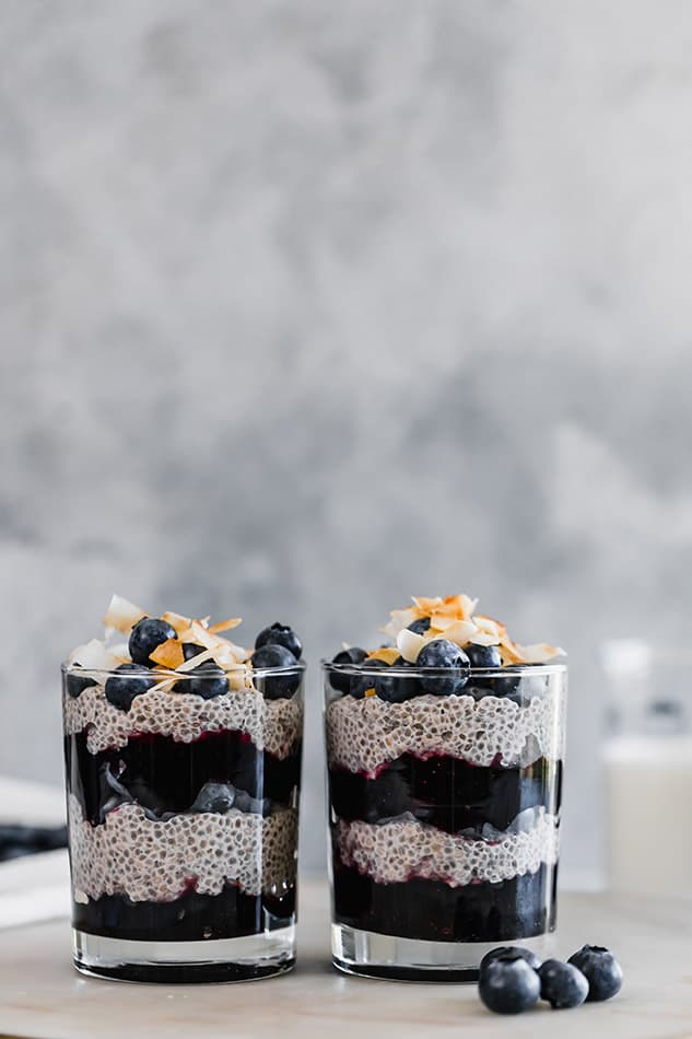 Front view of two jars of chia pudding with blueberries and coconut.