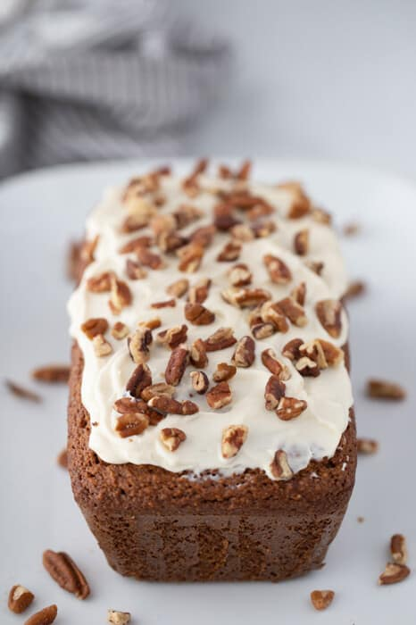 Side view of dairy-free frosted ginger loaf on a white plate