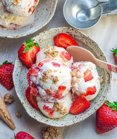 Top view of paleo strawberry cheesecake ice cream in a bowl with a wooden spoon
