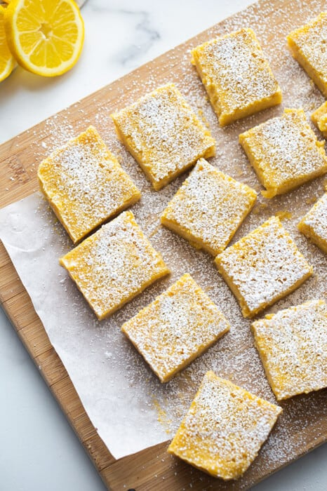 Overhead view of Lemon Bars dusted with powdered sugar on a wooden cutting board