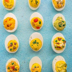 12 Various Deviled Eggs Evenly Spaced on a Blue Surface