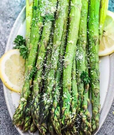Asparagus spears on a platter seasoned with salt and lemon