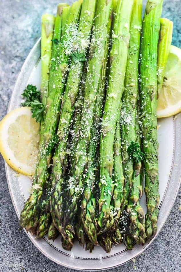Top view of Air Fryer Asparagus on a white plate with lemon wedges