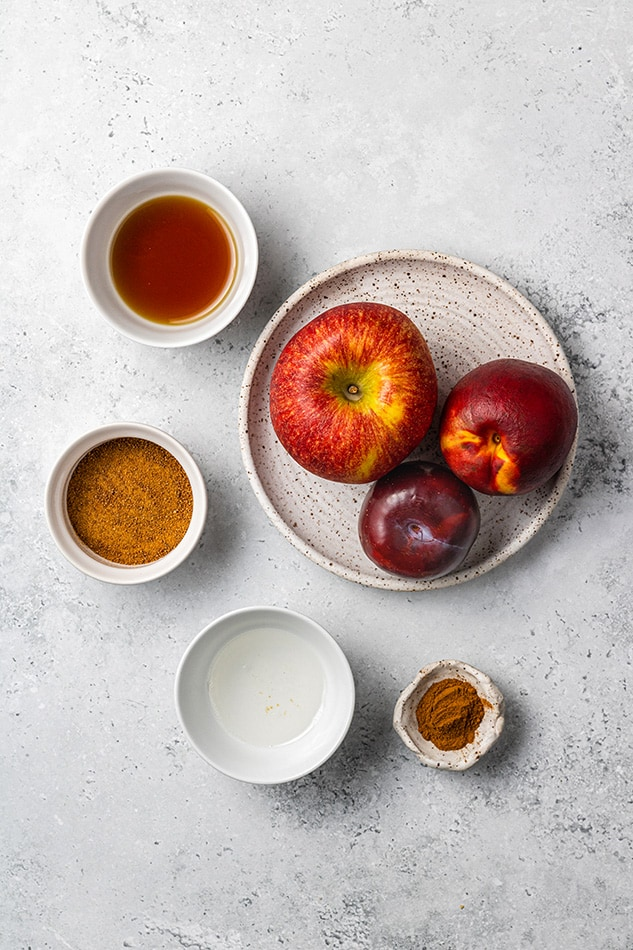 Overhead view of an apple, peach and plum on a plate surrounded with spices in bowls