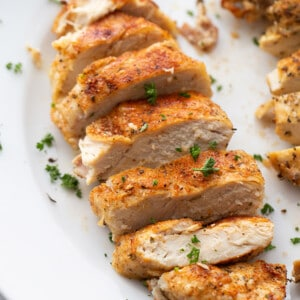 Side view of cut chicken breast on a white plate